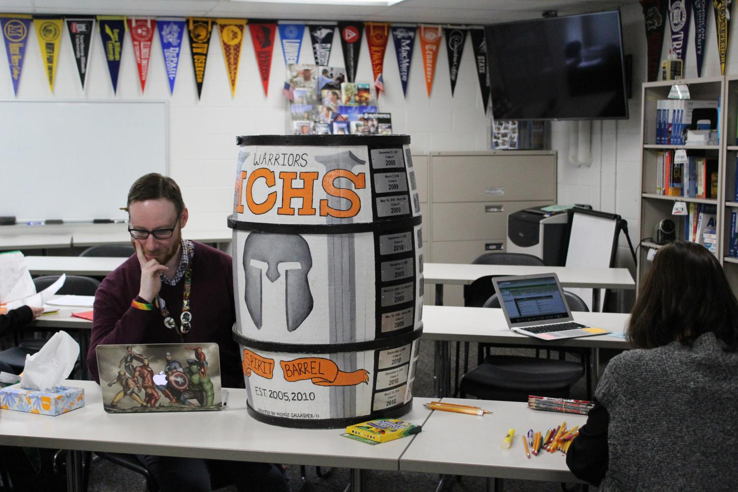 Curtis Menke, former Student Council Advisor and lover of school spirit, sits with his beloved Spirit Barrel.