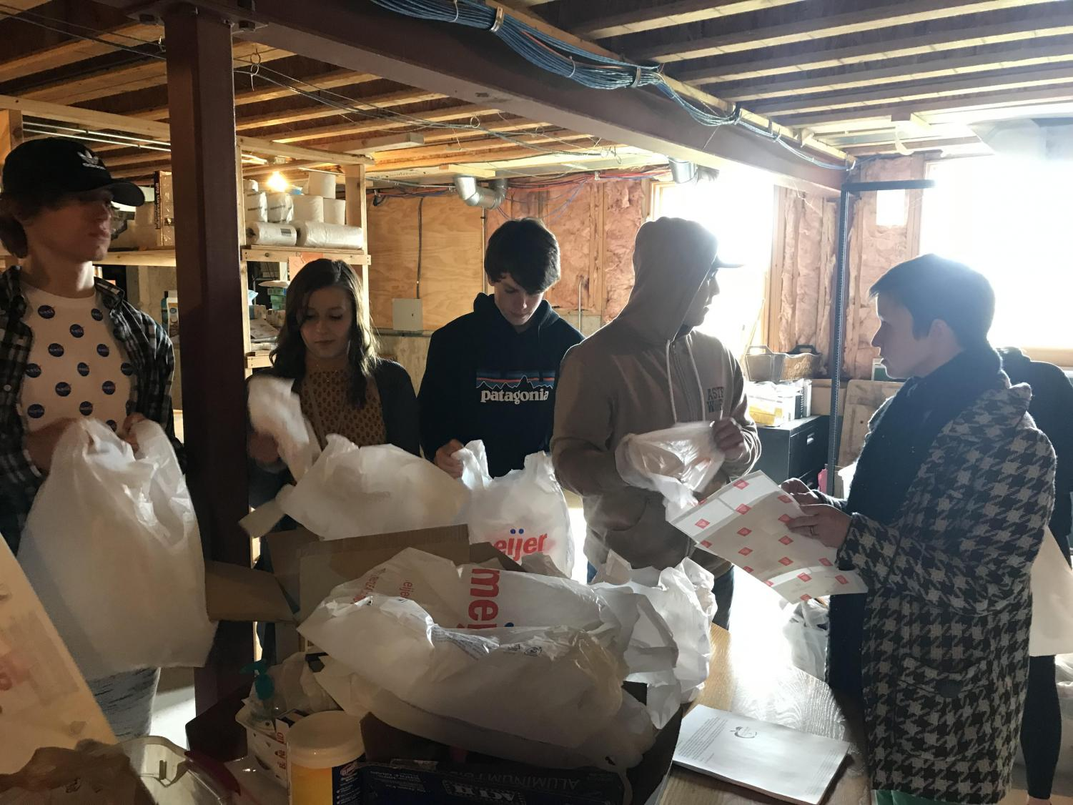 Food for Thought volunteers, Braeden Bromley, Julia Zickus, Kyle Hoskins, and Josh Duarte, meet in the basement of the Board of Education to assemble food bags to distribute to students.