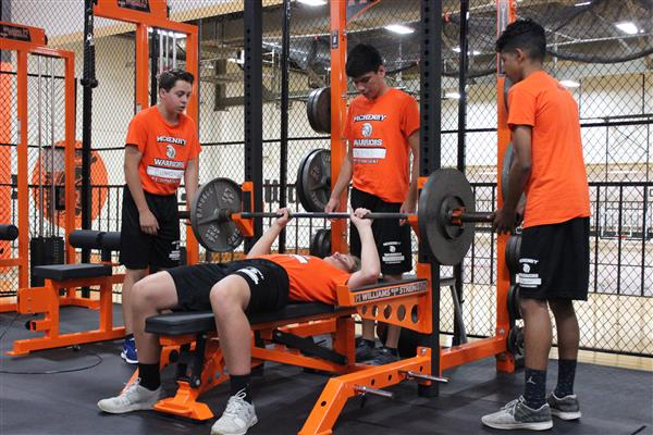 (L-R) Evan Cummings, Tyler Thomas, and Enrique Ravelo assist their classmate during a lifting session.