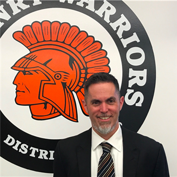Dr. Jeffry Prickett stands in front of the McHenry Warriors sign, showing his spirit.