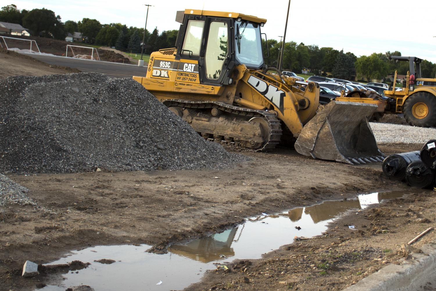 Construction equipment sits idle beside a mud pit in late August where the district hopes 10 new tennis courts will be constructed before winter