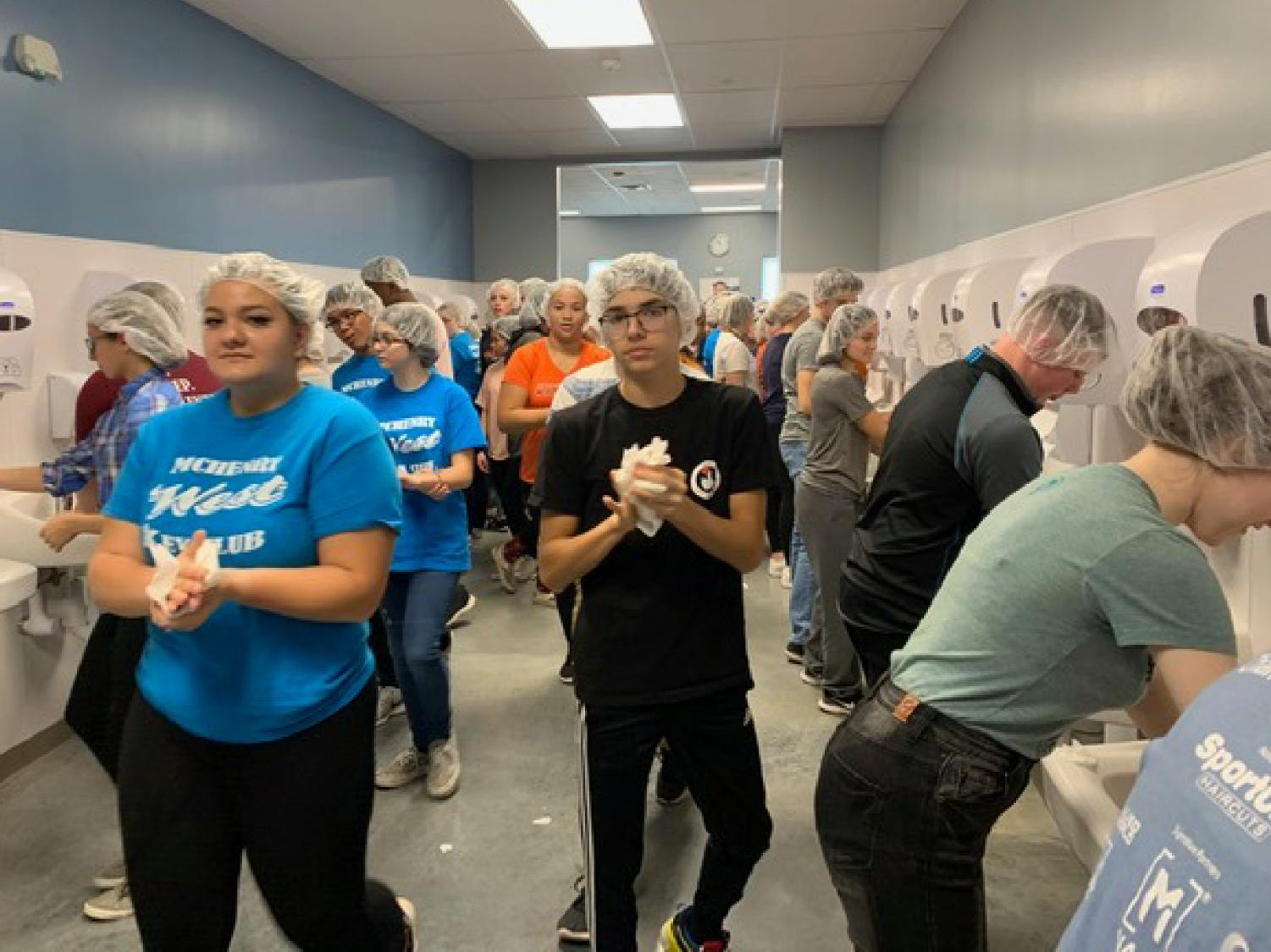 Volunteers from West's Key Club sanitize their hands before packing meals for Feed My Starving Children in Libertyville.