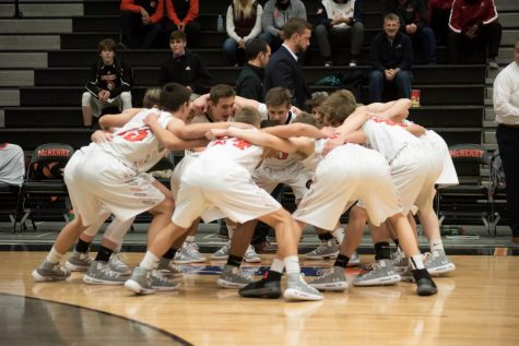 Cheering with their arms around each other, the 2018-19 varsity boys basketball team pumps each other up before a game against Marian-Central on November 28, 2018.  Last year's team finished their season with a record of 2-28.
