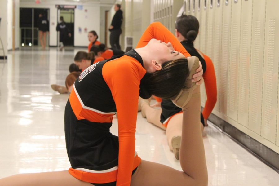 Logan LaRose stretches with the varsity dance team in the hallways at West Campus before their performance. The dance team hosted the Fox Valley Conference championship at West Campus on January 15.