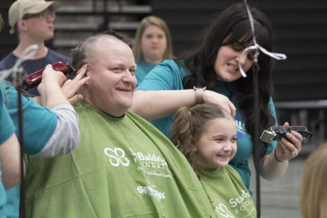 Carl Vallianatos, assistant superintendent of curriculum and instruction, has his head shaved alongside his daughter Sophie during the 2019 Community Shave in the West Campus Main Gym on March 21.