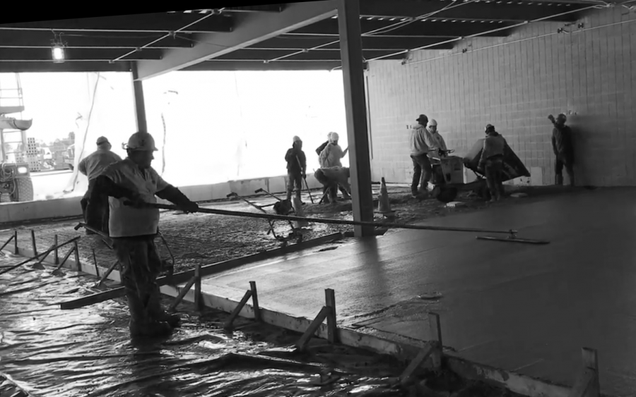 Construction workers smooth concrete floors for the first floor of the new extension at West Campus on April 10. Construction remains on schedule despite school being closed for the remainder of the school year.