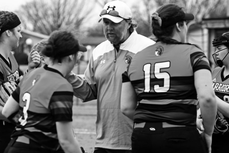 Assistant coach Ray Currie congratulates last year's varsity softball team between innings during a game on April 6, 2019. Spring sports and other extracurriculars were among cancellations in the wake of coronavirus.