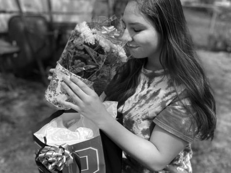 """Adopted"" senior Sydni Johns opens a care package from Linnea Schwartz in her front yard on May 7. John is one of dozens of seniors ""adopted"" by the community as their senior year ends during a state-wide shelter-in-place order."
