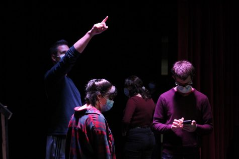 "Derek Galvicius gives lighting instructions while Alayna Majkrzak and David Henry look over their lines during a rehearsal for ""The Living"" on October 20."