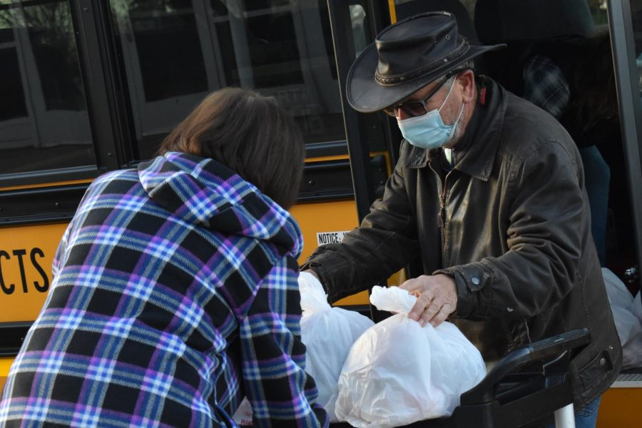 A food service worker helps a driver load lunches to be delivered to MCHS students outside of West Campus on November 20.