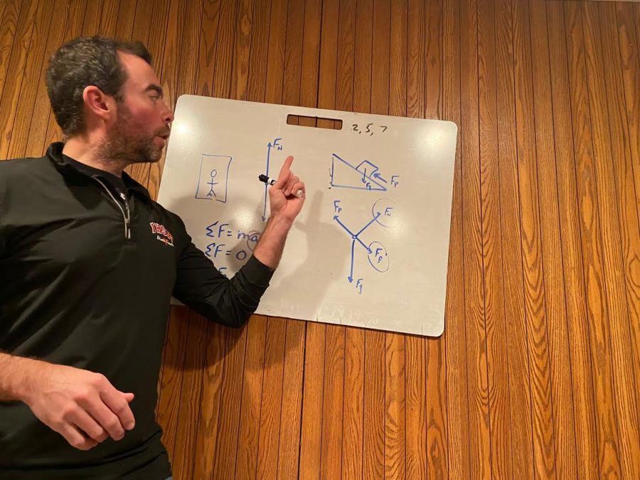 West Campus science teacher Mr. Ryan Ellison walks his students through an equation on a whiteboard in his home. Some MCHS teachers work from home part time or full time, and some prefer to teach in their classrooms.