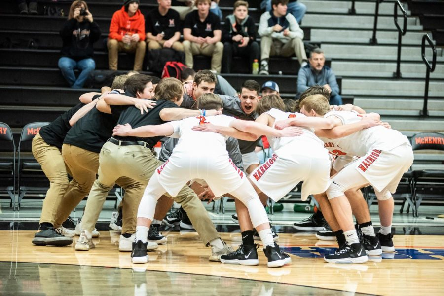 The+2019-20+boys+basketball+team+gets+fired+up+before+a+game+against+Cary-Grove+on+January+8+in+the+West+Main+Gym.+This+season%27s+basketball+season+has+been+disrupted+due+to+COVID-19+restrictions+handed+down+from+both+the+governor+and+the+IHSA.