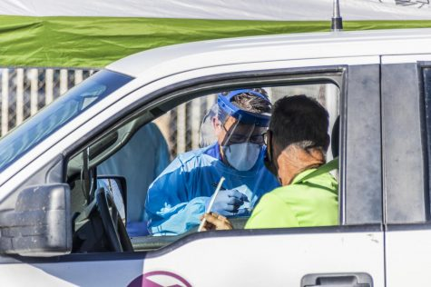 Health care workers collect saliva samples at a drive-up testing site in Arizona in November. Since then, COVID cases have dropped significantly in most states, including Illinois.