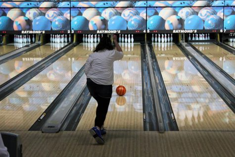A girls bowler rolls a ball down the lane at Raymond