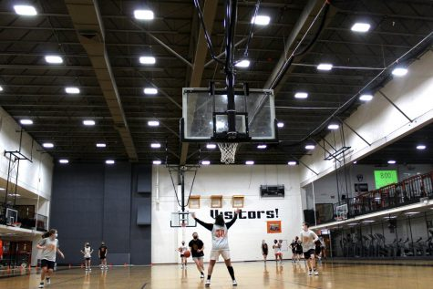 The girls basketball team practices in Buckner Gym at West Campus on March 3 while other athletes train in the weight room. Two- and three-season athletes have had to make tough decisions about which sports to play — and which not to play — during overlapping seasons.
