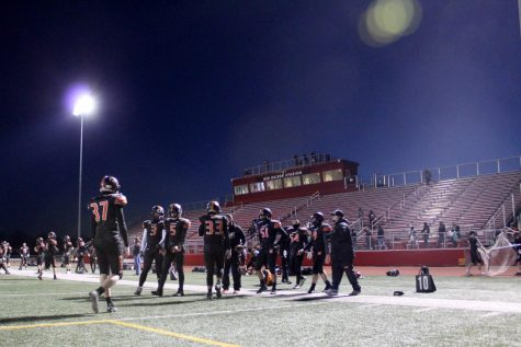 Varsity football players warm up before the first football game of a delayed season against Prairie Ridge on March 19 at Huntley High School.
