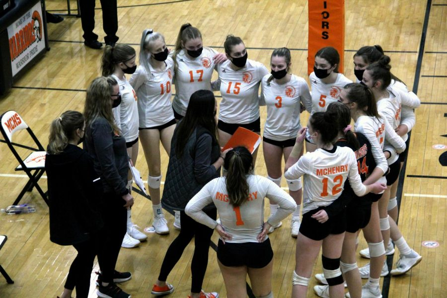 The varsity volleyball team meets mid-court to strategize during a game against Johnsburg on March 24 in the East Campus main gym.