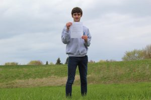 Freshman Daniel Thomas stands outside of West Campus with his Greentastic climate agreement. Thomas penned the agreement with environmental club in an attempt to make a positive change at MCHS.