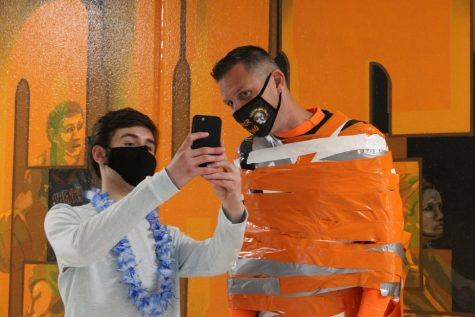 Students pose with Derek Galvicius during Duct Tape the Teacher, which concluded Homecoming week on April 23 outside the West Campus cafeteria.
