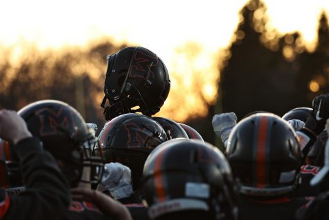 The varsity football team huddles before a home game and stokes their team spirit against Huntley at McCracken Field on April 1. Several senior athletes at MCHS, including football players, intend to play college-level sports next year.