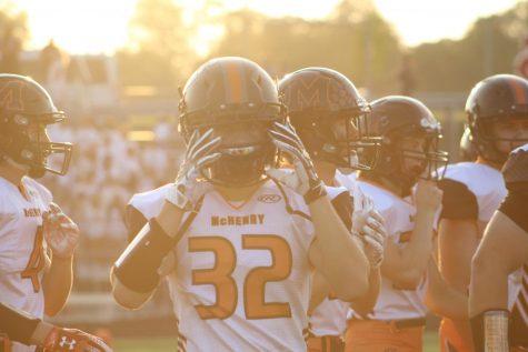 Dylan Drumheller puts on his helmet before the first varsity football game of the 2020-21 season on August 27 at Prairie Ridge High School.