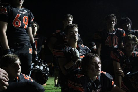The varsity football team meets in the shadows behind the stadium during halftime at the first home game of the season on September 3 at McCracken Field.